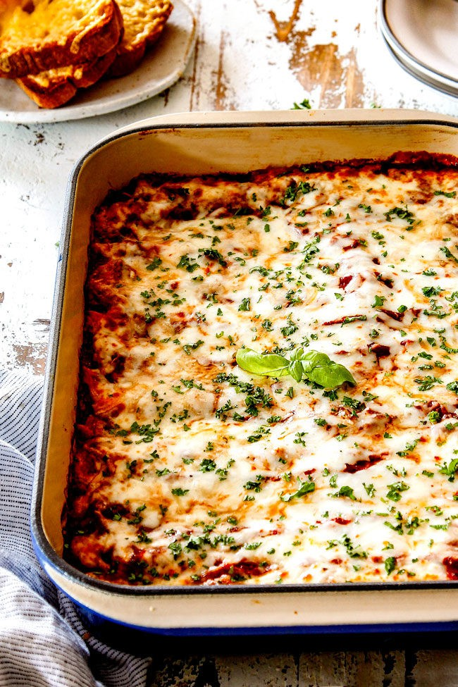 up front view of homemade manicotti in a blue casserole dish