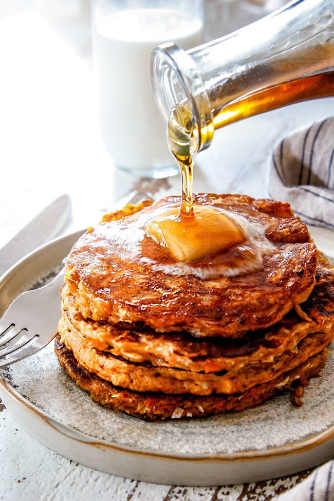 far away shot of pouring syrup over sweet potato pancakes with a slab of butter on top