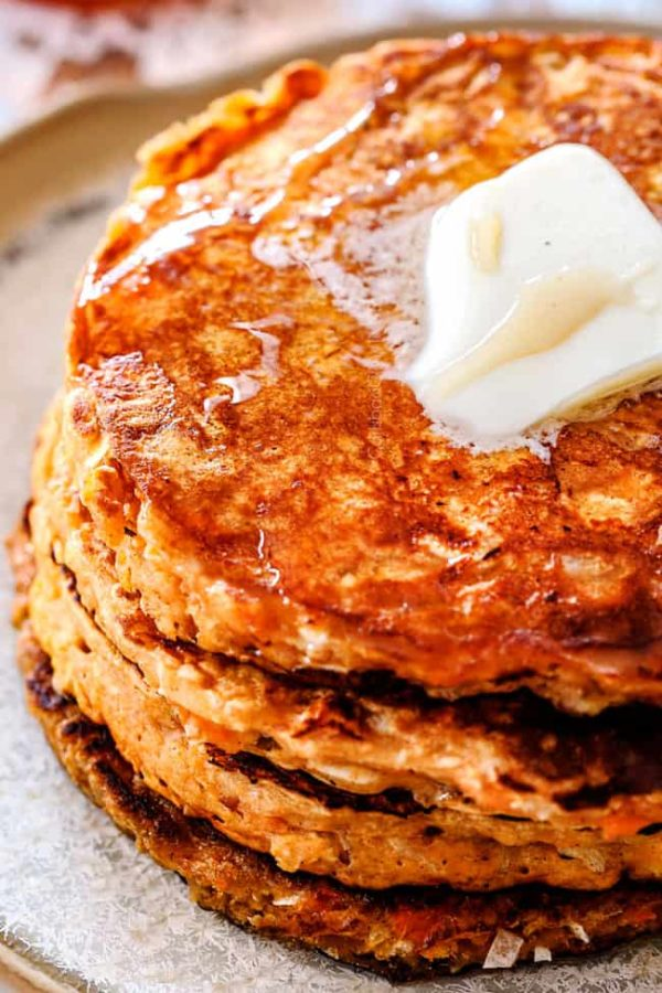 up close of sweet potato pancakes on a plate with syrup drizzled on top