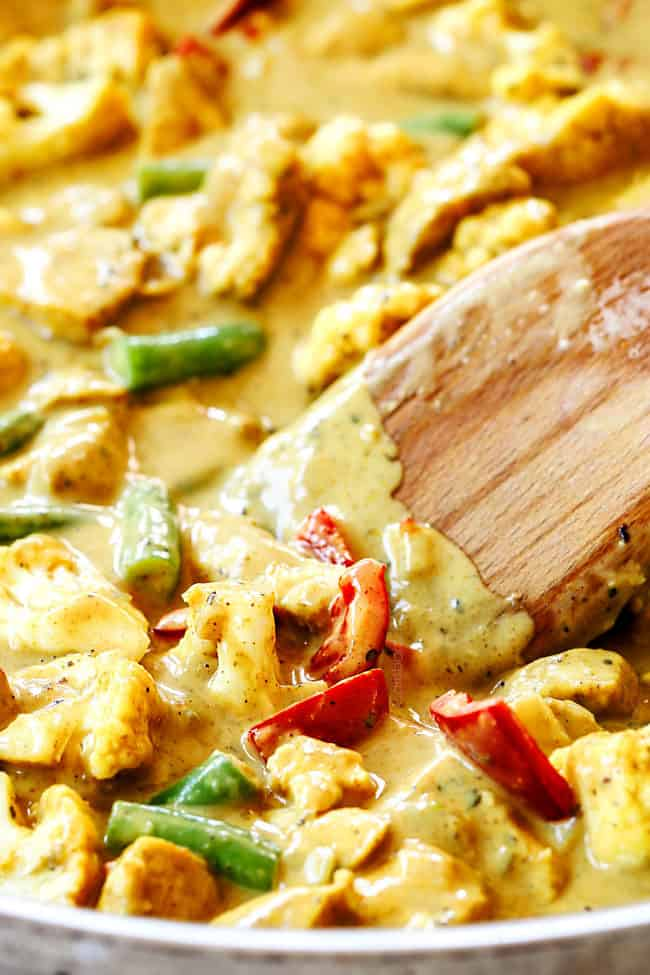 up close of a spoon stirring creamy coconut curry chicken with vegetables