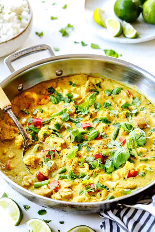 far away view of a stainless steak skillet of creamy coconut curry chicken recipe garnished with cilantro and lime
