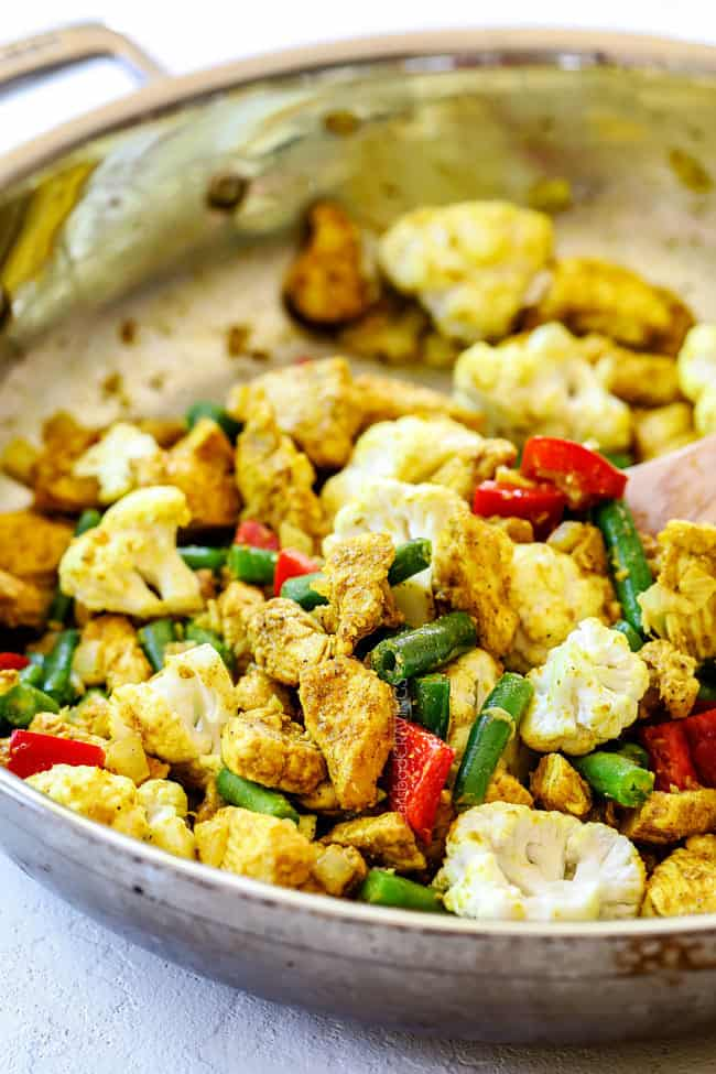 showing how to make coconut curry chicken recipe by cooking curry powder, chicken and vegetables in a skillet
