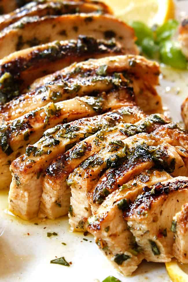 showing how to make grilled chicken salad recipe by thinly slicing grilled chicken breasts.