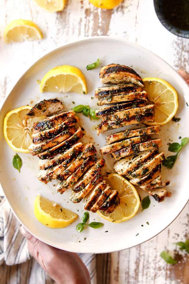 lemon basil chicken sliced on a white plate with lemon slices and basil