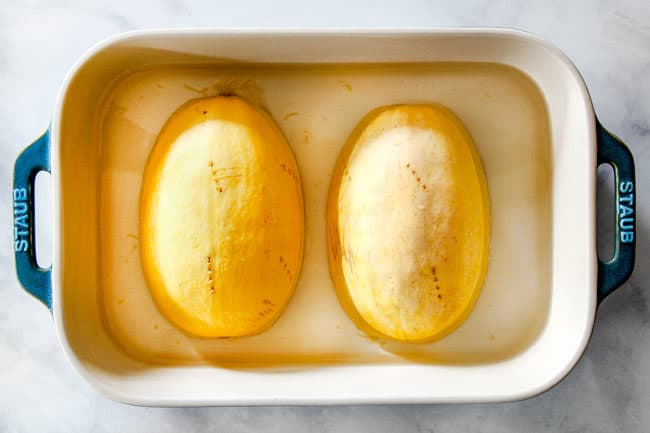 showing how to cook spaghetti squash in the microwave by placing two spaghetti squash halves cut side down in water in a pan