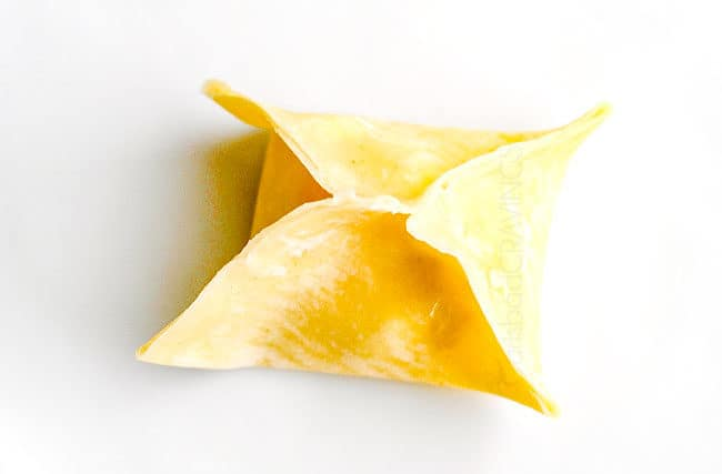 showing how to make cream cheese wontons by folding up all corners of wontons