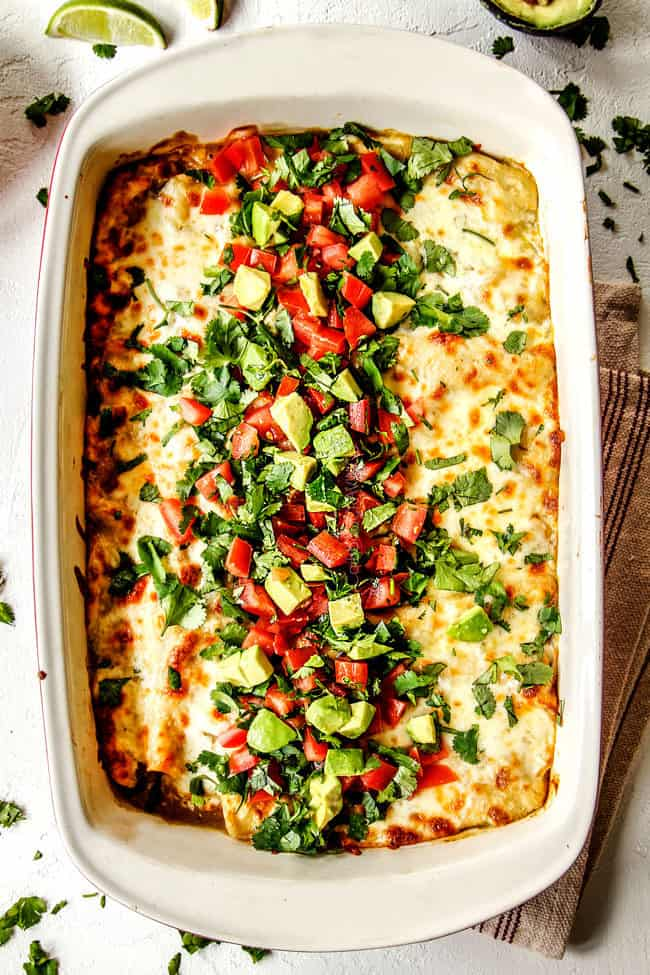 top view of enchiladas verdes casserole topped with cheese, cilantro, tomatoes, avocados