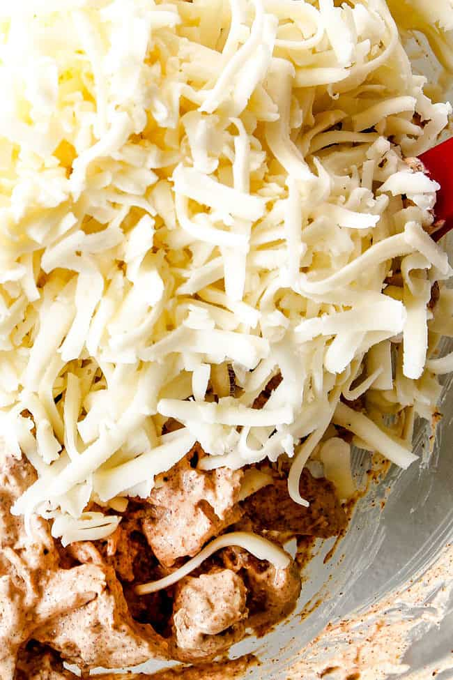 showing how to make chicken enchiladas by adding cheese to chicken in a glass bowl