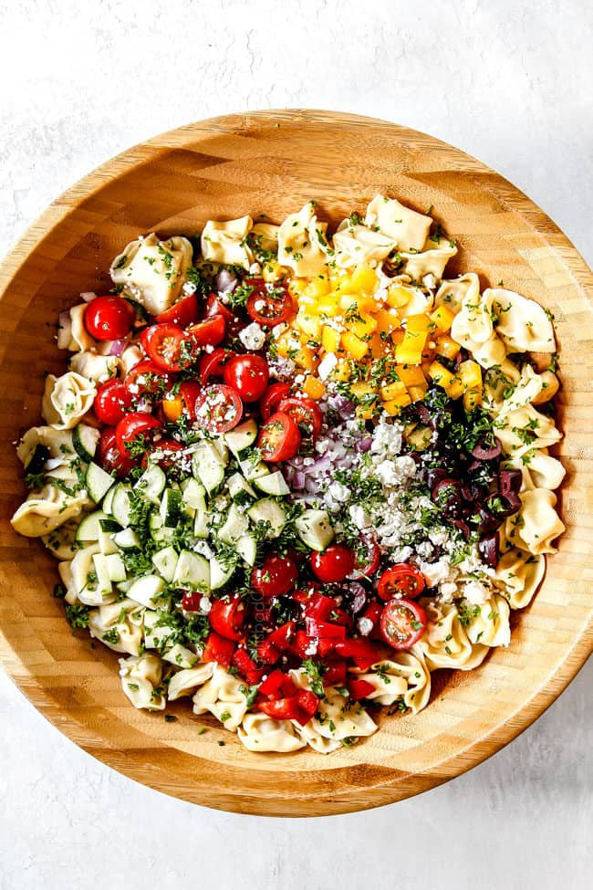 showing how to make Greek Past Salad by adding pasta, tomatoes, olives, bell peppers, red onions, cucumbers to a wood bowl