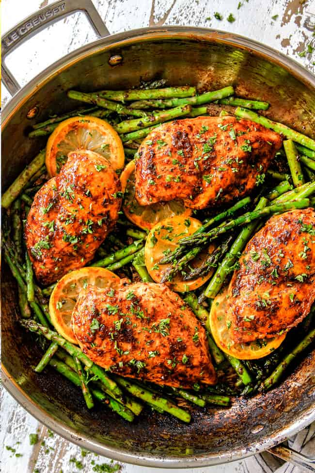 top view of lemon pepper chicken and asparagus in a skillet