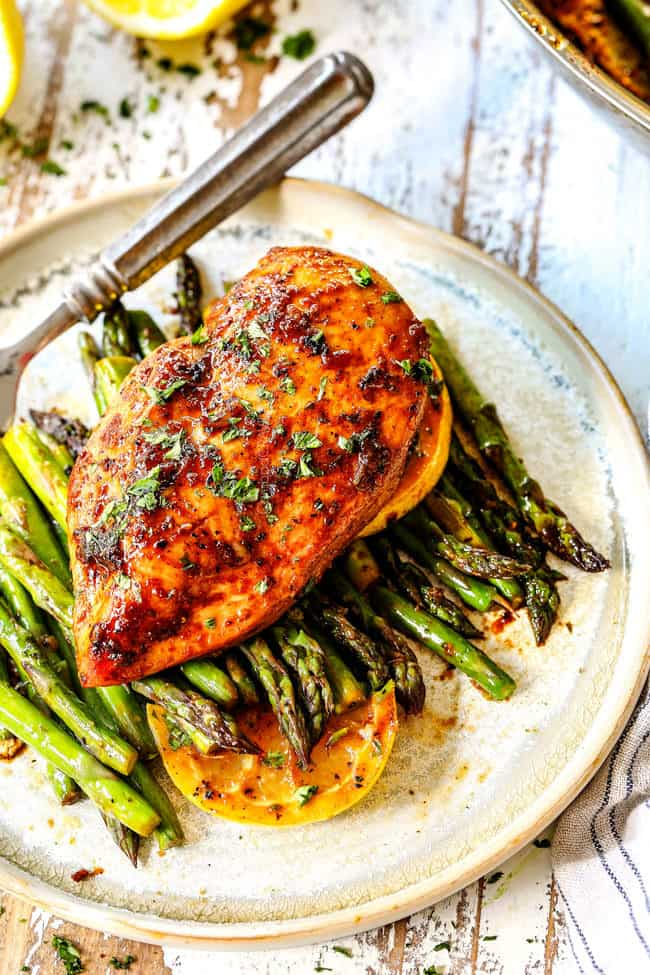 top view of a piece of lemon pepper chicken and asparagus on a plate garnished by lemons with a fork