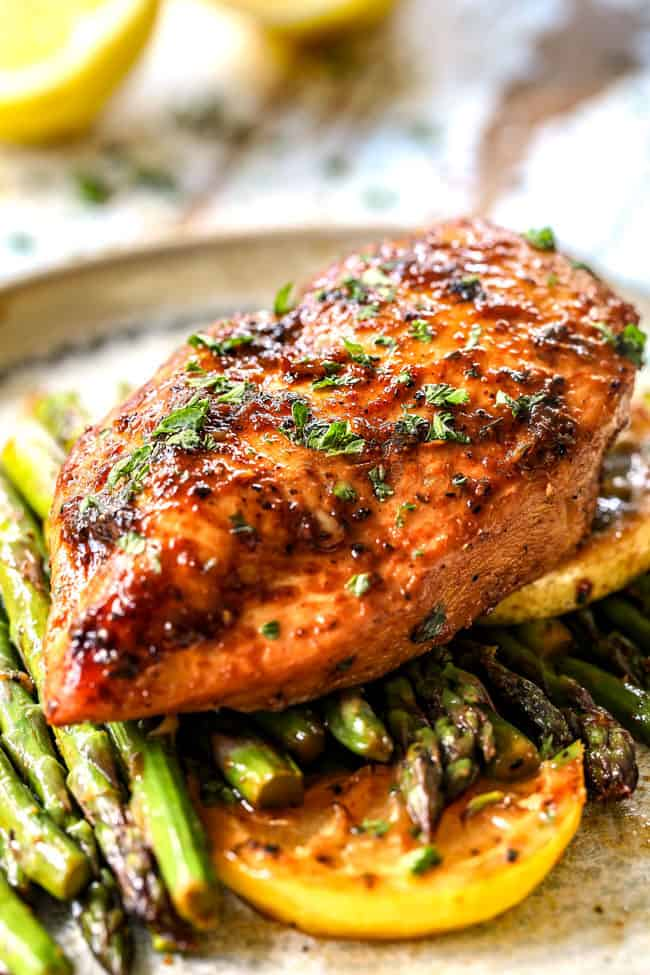 up close of a piece of lemon pepper chicken and asparagus on a plate garnished by lemons