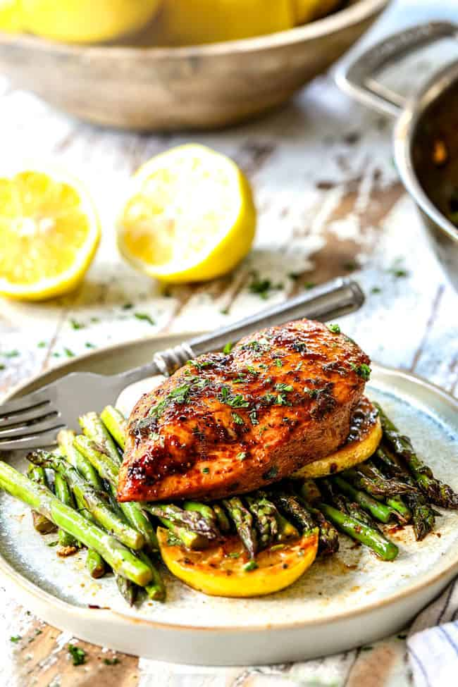 a piece of lemon pepper chicken and asparagus on a plate garnished by lemons