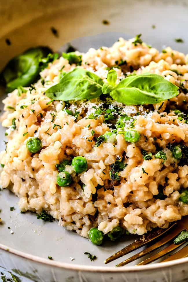 up close of a serving of Parmesan spinach risotto recipe on a grey plate garnished with parsley
