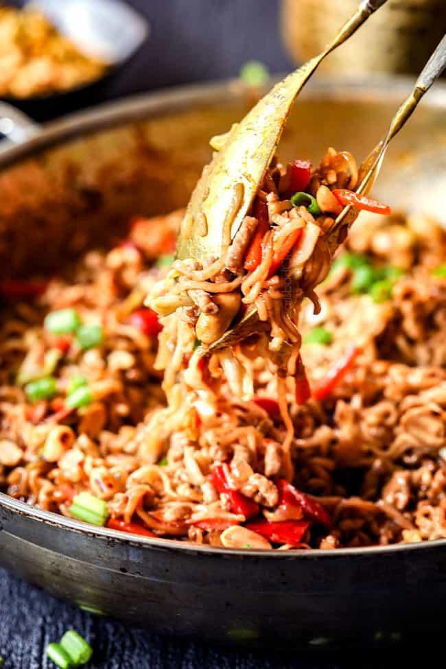 tongs picking up spicy pork ramen recipe
