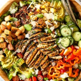 top view of Chicken Caesar Salad in a wood bowl with croutons, grilled chicken and Caesar dressig