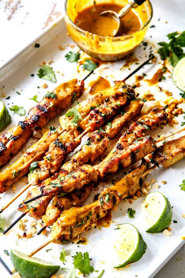 far away view of grilled chicken satay on a platter with peanut sauce