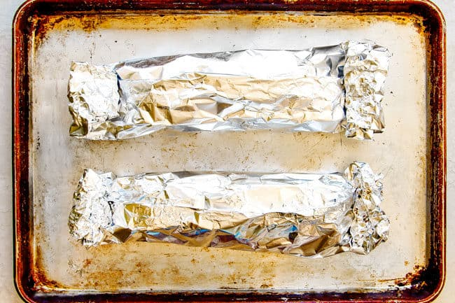 showing how to bake pork tenderloin in the oven with foil by wrapping up pork tenderloin in foil