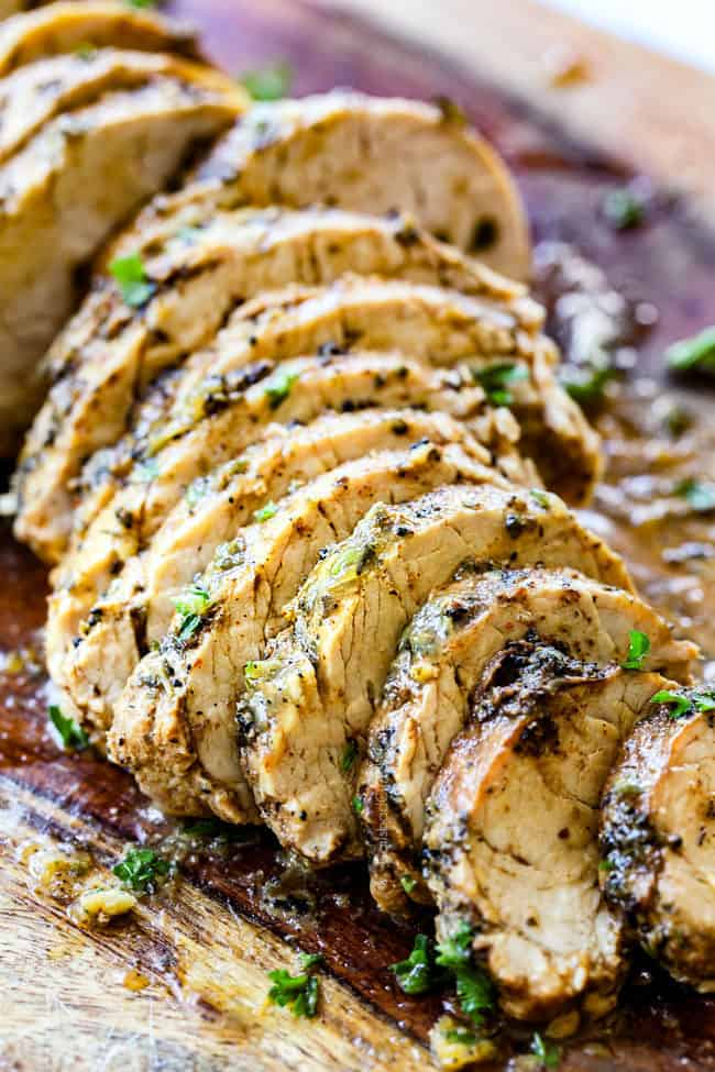 juicy baked pork tenderloin recipe sliced on a cutting board