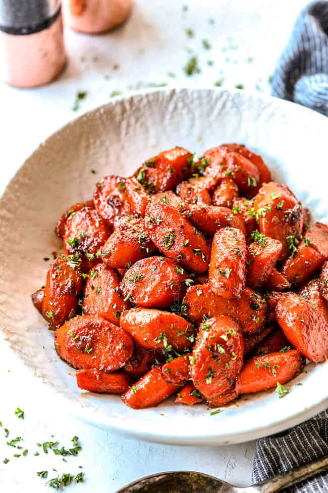 side view of glazed carrots recipe in a white serving bowl garnished by parsley