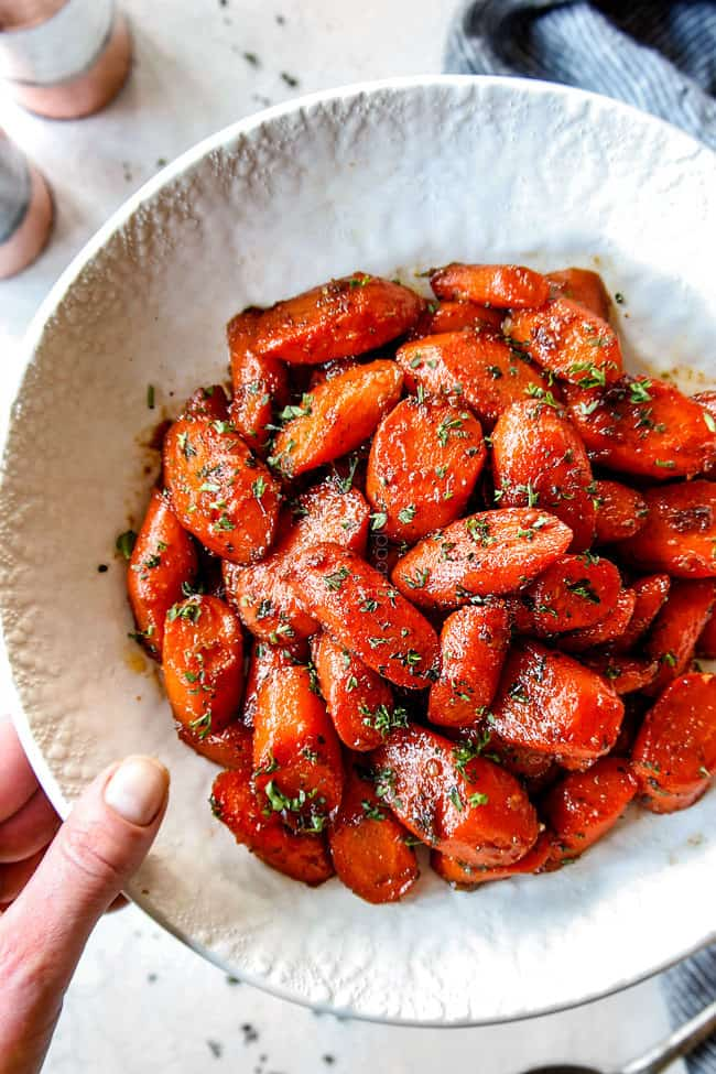 a hand holding a white bowl of brown sugar glazed carrots