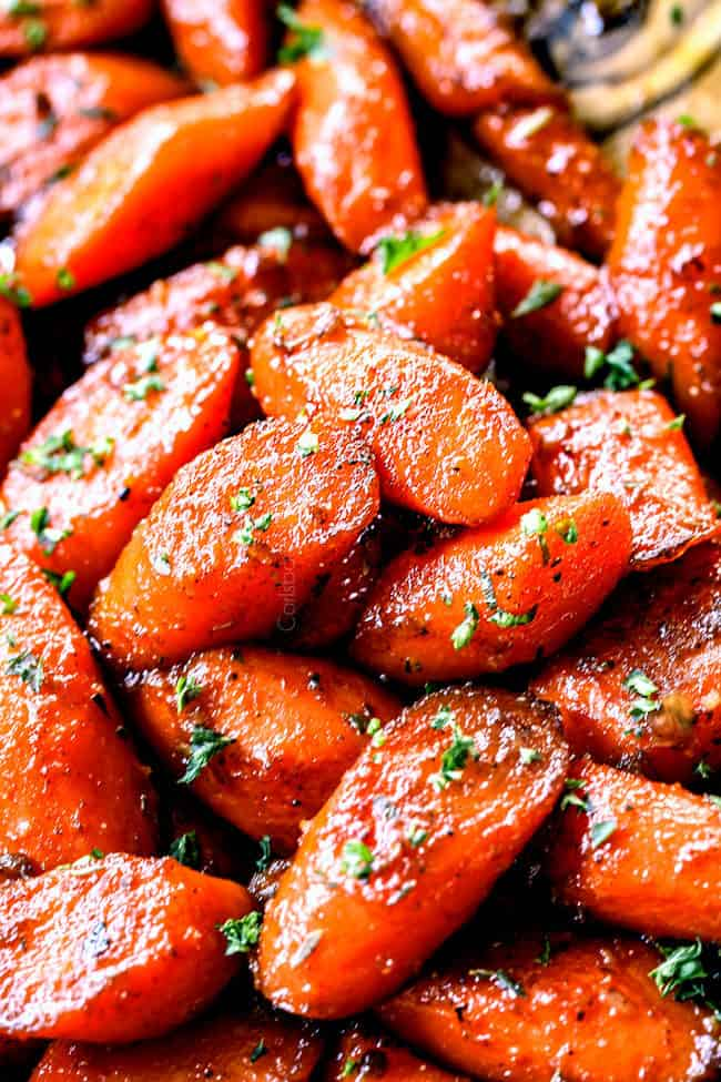 up close of glazed carrots recipe in a stainless steel skillet with a wooden spoon