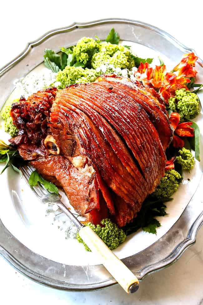 side view of honey glazed ham on a white platter