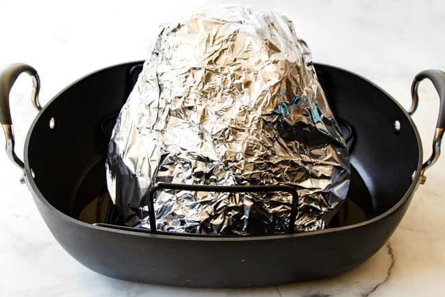 showing how to make honey baked ham recipe by wrapping ham tightly in foil