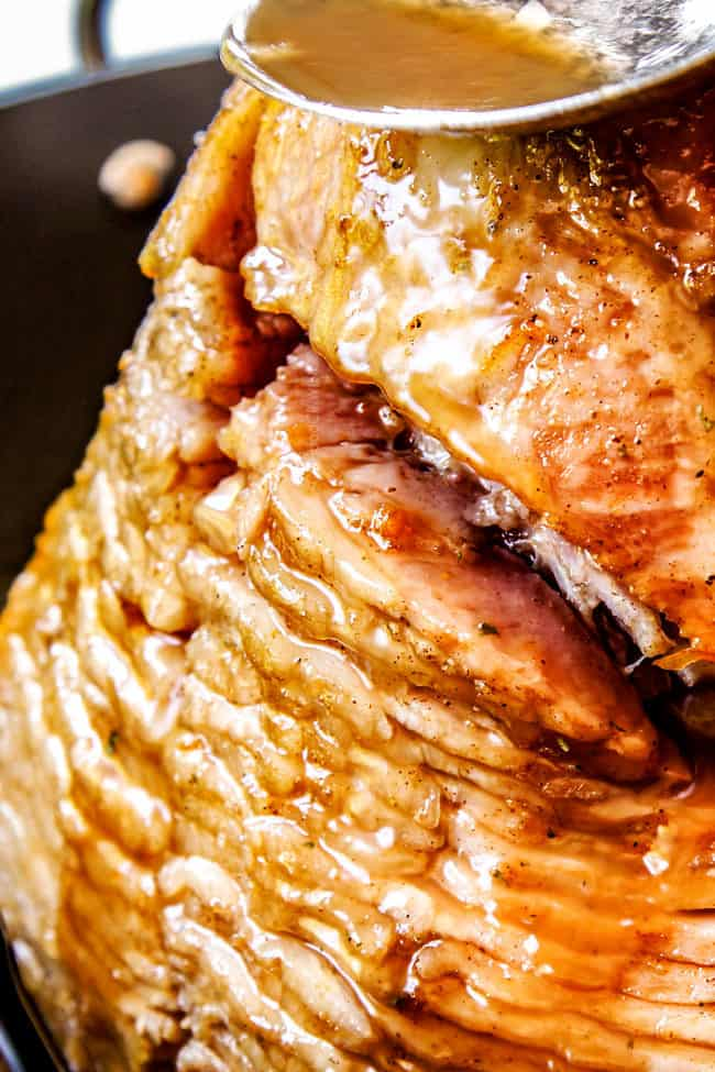 showing how to make honey baked ham by basting with juices