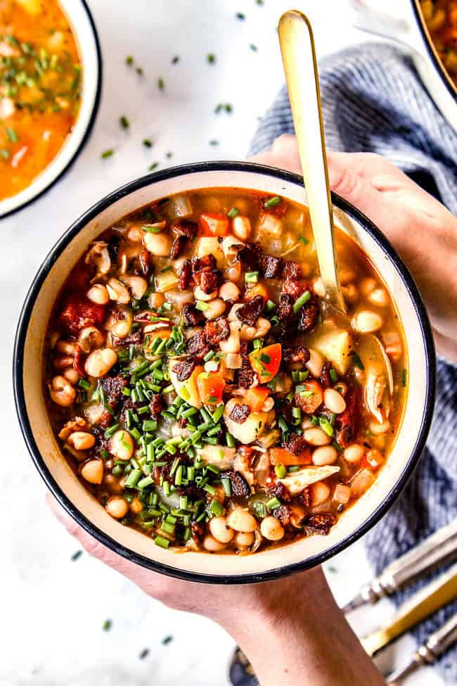 two hands holding slow cooker navy bean soup