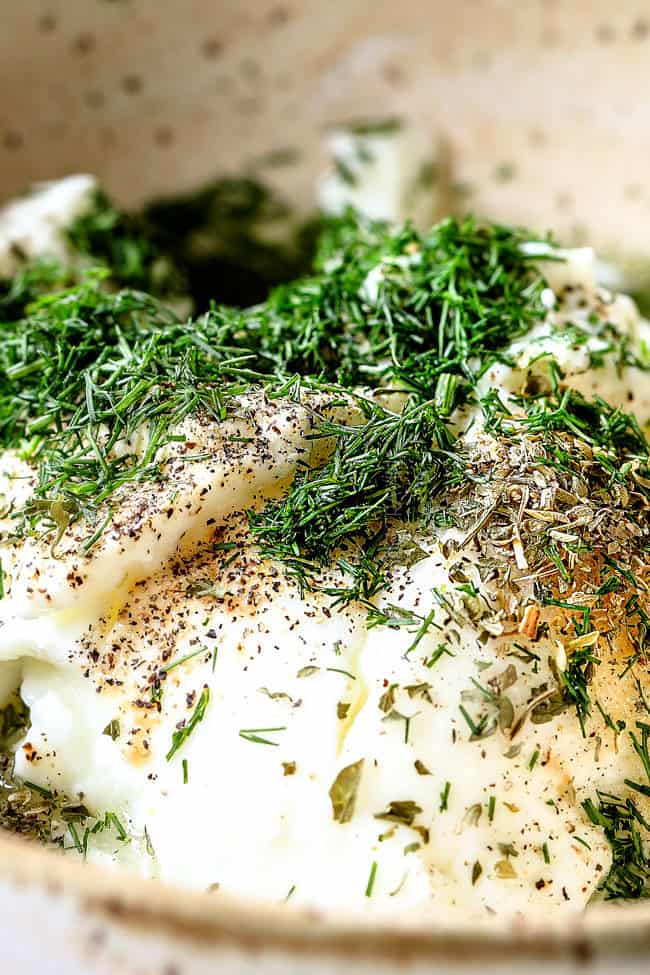 showing how to make healthy dill sauce for salmon by adding Greek yogurt, dill, lemon juice, vinegar, oregano, salt and pepper to a bowl