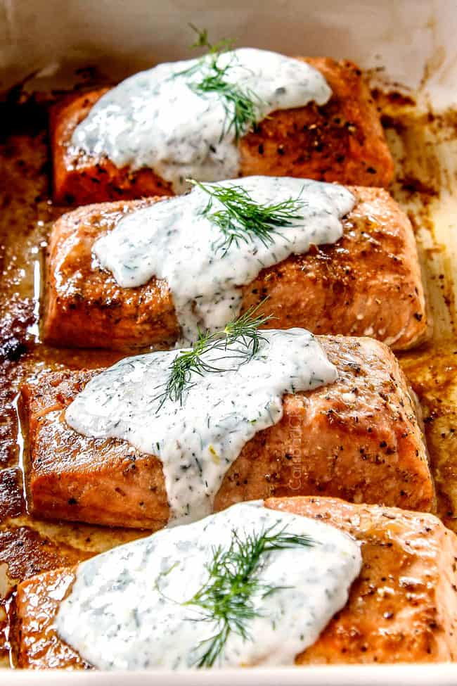 side view of healthy oven baked salmon fillets in a row topped with dill sauce