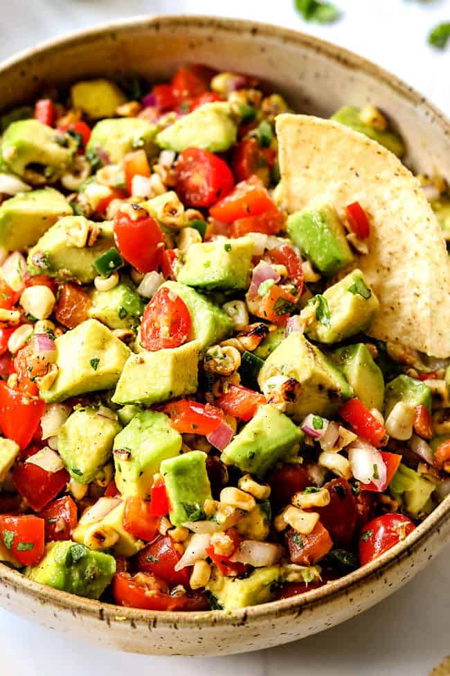 a bowl of easy avocado corn salsa with a chip