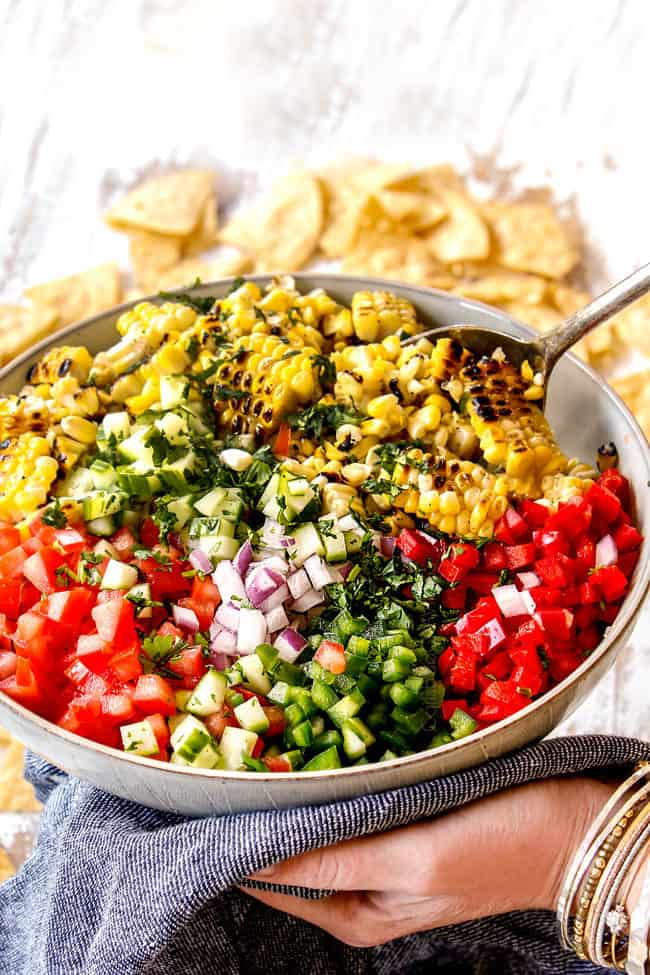 side view showing how to make corn salsa by adding corn, onions, tomatoes, bell peppers jalapenos, lime juice and cilantro to a bowl