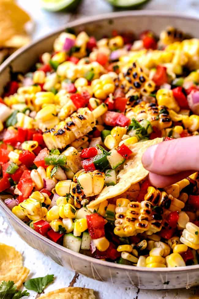 a hand scooping a chip into canned corn salsa