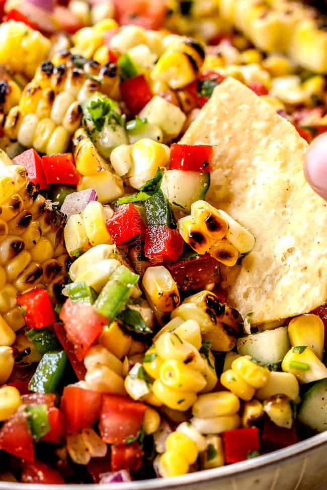 up close of scooping easy corn salsa recipe with a tortilla chip
