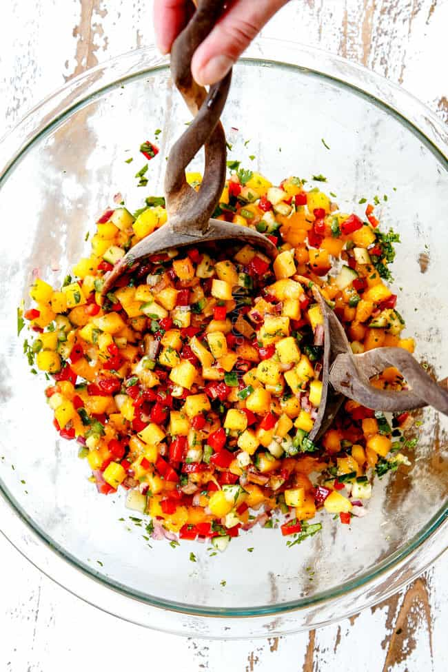 showing how to make mango salsa with two wooden spoons tossing ingredients together