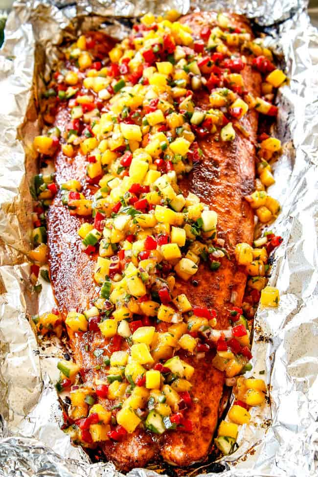 showing how to use mango salsa by adding it on top of salmon