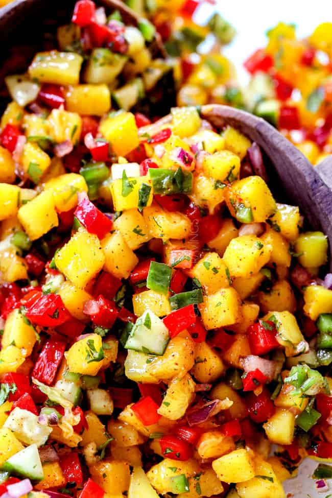 up close of two servings spoons scooping up mango salsa recipe