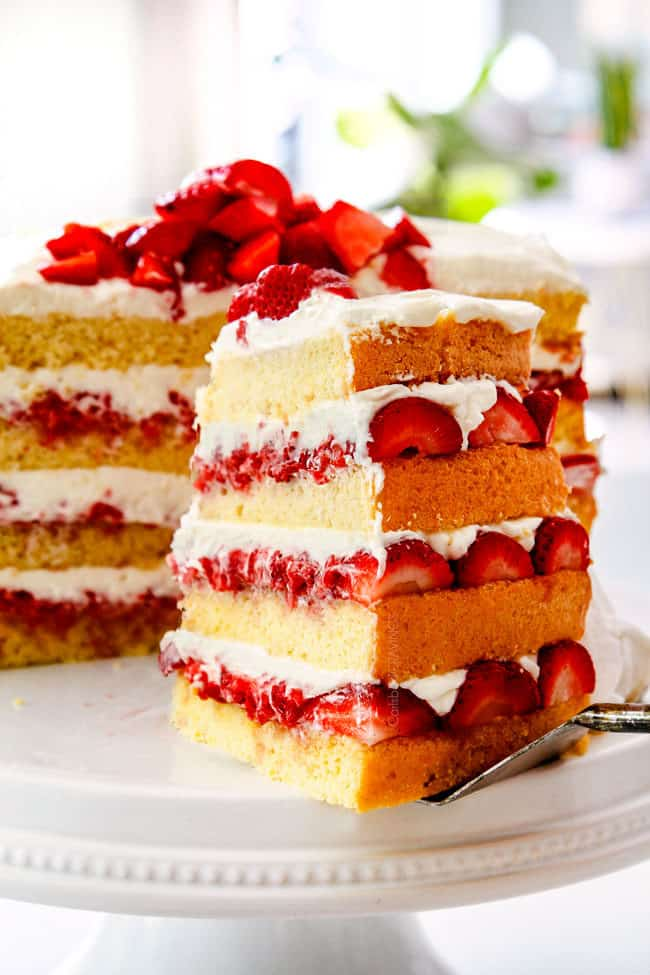 taking a slice of showing how to layer strawberry shortcake cake by