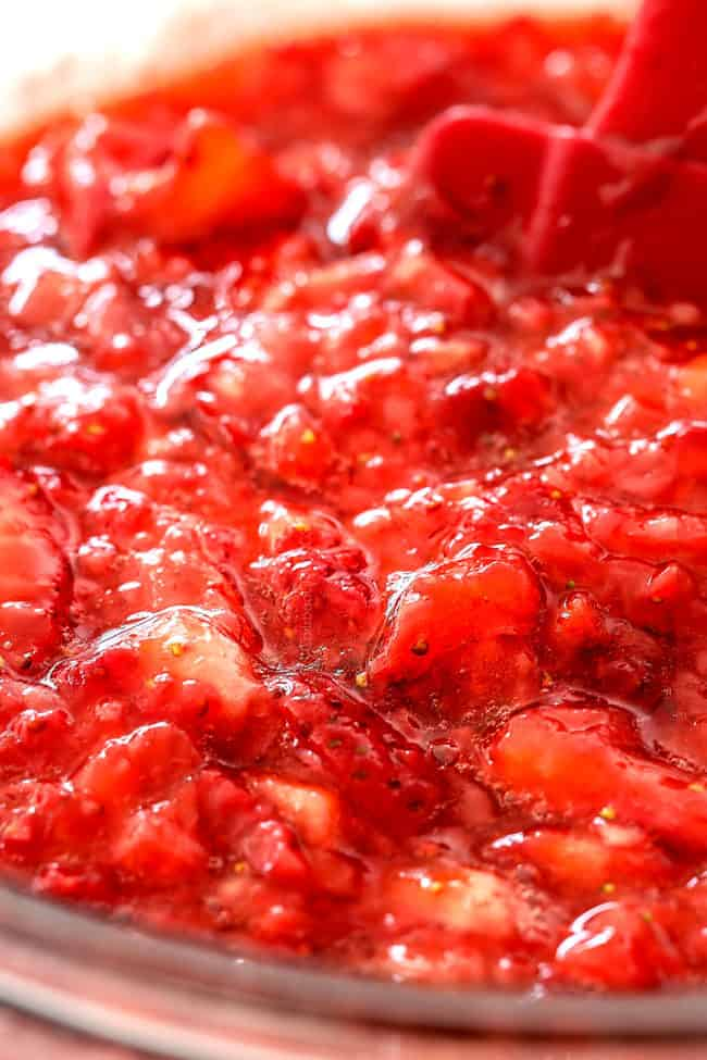 showing how to make strawberry shortcake cake by adding strawberry syrup to chopped strawberries