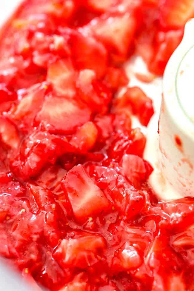 showing how to make strawberry shortcake cake by chopping strawberries in food processor