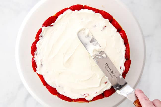 showing how to layer strawberry shortcake cake by adding whipped cream on top of the strawberries