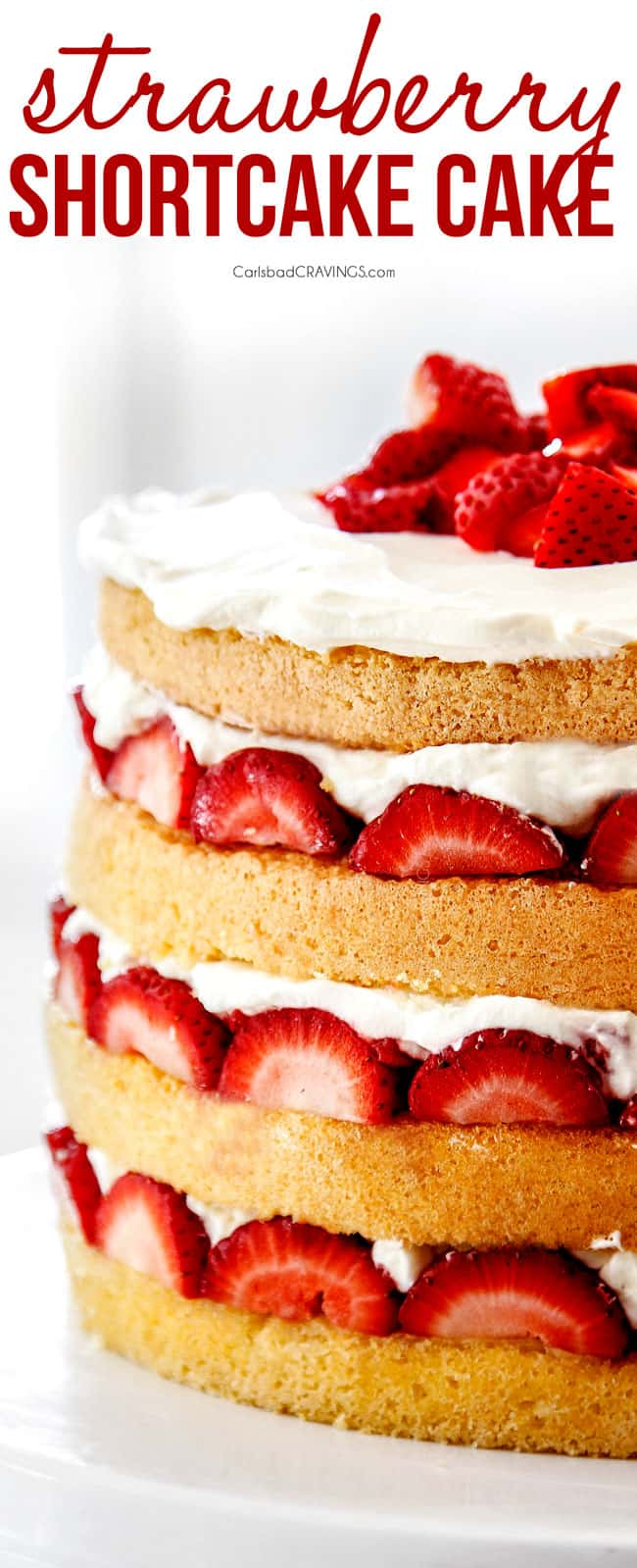 up close of strawberry shortcake cake with layers of sponge cake, strawberries and whipped cream