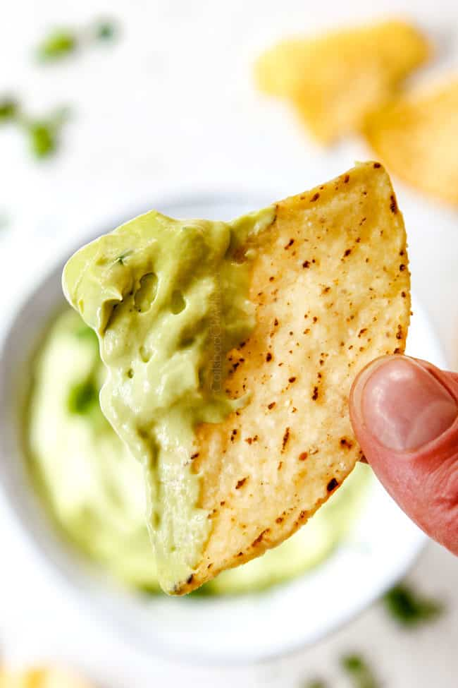 up close of a chip dipped in easy avocado crema