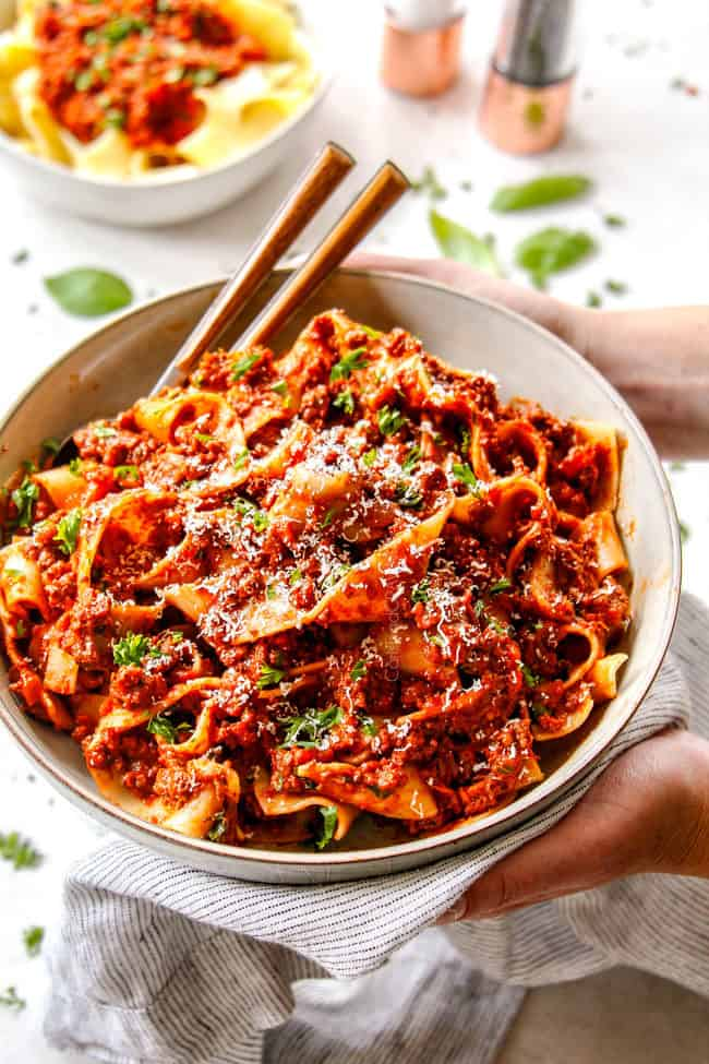 holding a bowl of pasta bolognese and garnishing with Parmesan and parsley