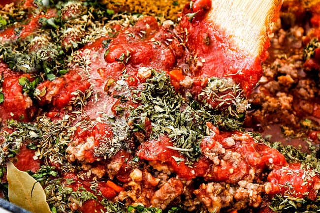 showing how to make authentic bolognese sauce by adding parsley, thyme, oregano, basil, crushed tomatoes to a pot