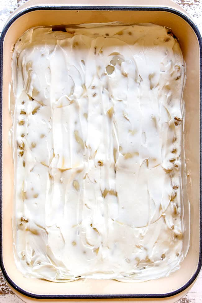 showing how to make Chicken Alfredo Bake by adding a layer of sour cream over pasta
