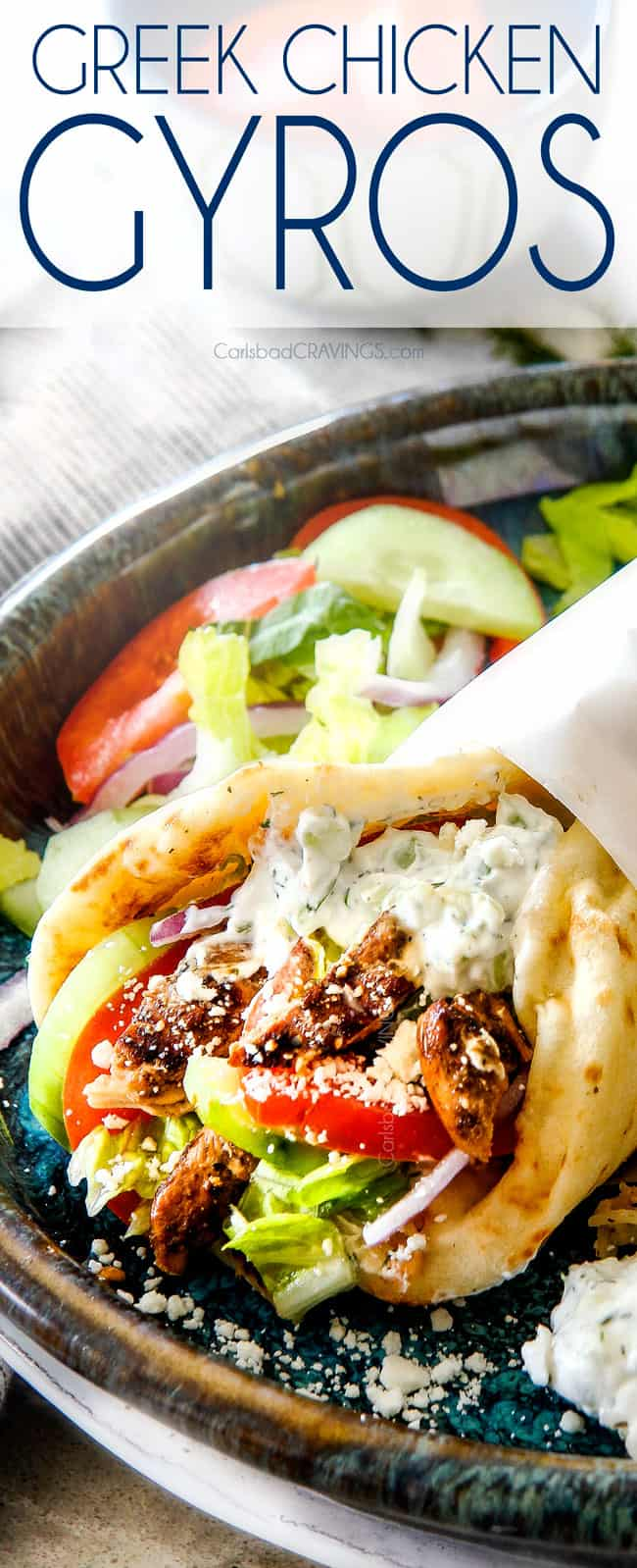 up close of a chicken gyro  with Greek chicken, tomatoes, lettuce and tzatziki wrapped in paper