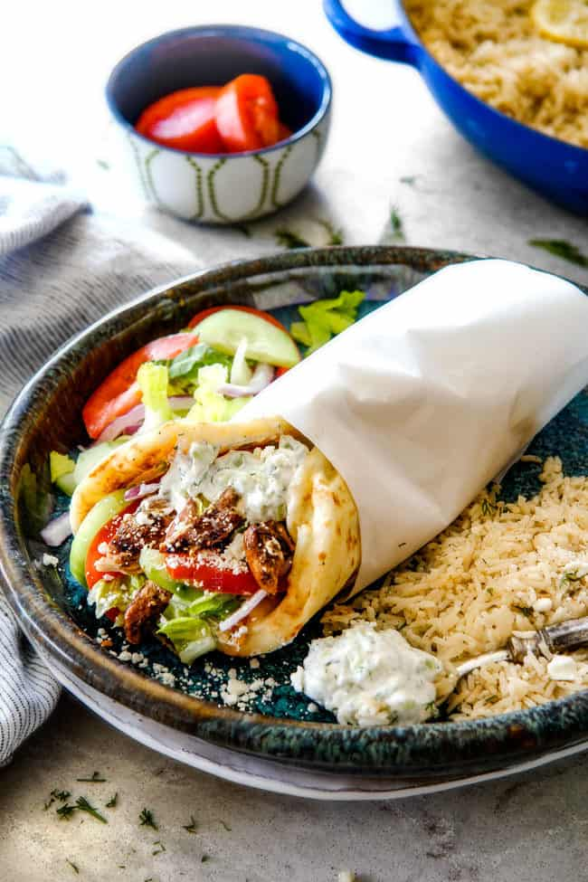 showing  what to serve with chicken gyros with a gyro on a plate with Greek rice and salad